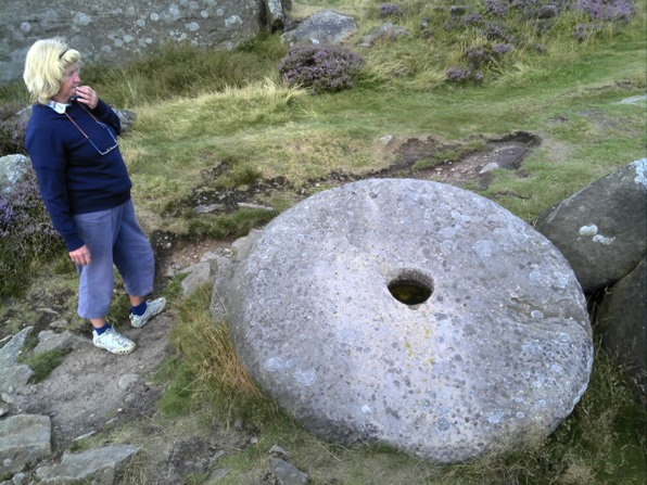 Jo pondering on a large conical shaped wheel on Curbar Ridge, Derbyshire