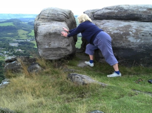 Jo trying to push this large stone over the edge. Curbar Ridge, Derbyshire