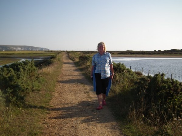 Joanna walking on the sea wall which she has one every year for sixty years